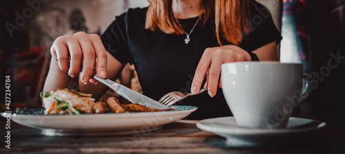 Fotografia woman hands with fork and knife eating beef steak in cafe