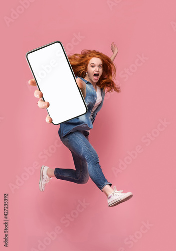 Fotografia Excited redhead woman having fun, jumping,demonstrating mobile phone with empty