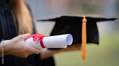 Close-up shot of a university graduate holding a degree certification to shows and celebrate education success on the college commencement day. Education stock photo - fototapety na wymiar