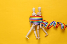 Lgbt Relationships. Two Puppets On Yellow Background With A Rainbow Ribbon