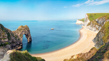 Aerial View Of Durdle Door Natural Formation At UNESCO Heritage Jurassic Coast. The Isle Of Portland Can Be Seen On The Horizon. Copy Space In Blue Sky.
