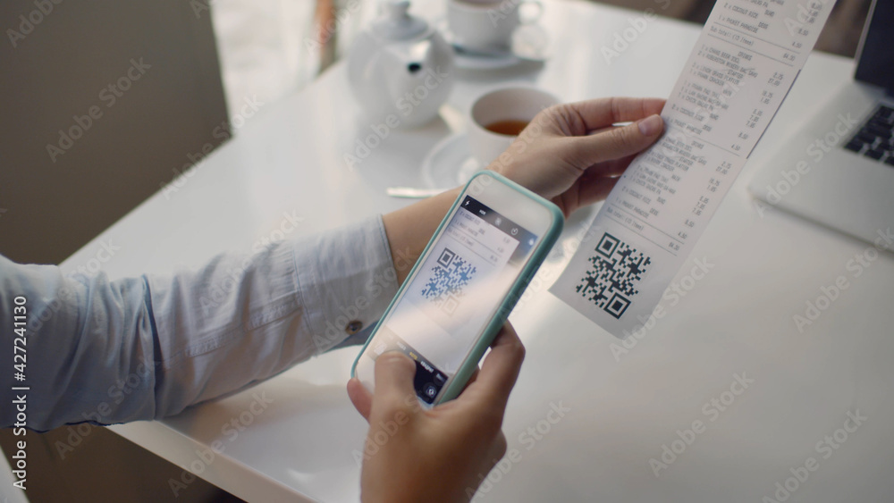 Fototapeta Close up of woman using smartphone and scanning qr code on cash shop receipt