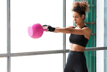Close Up Of Young Beautiful Woman Doing Crossfit Russian Swing In A Gym With A Pink Kettlebell. White Background. Horizontal