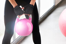 Close Up Of Young Beautiful Woman Legs Doing Crossfit Russian Swing And Pink Big Ball On The Floor Of A Gym With A Pink Kettlebell. Horizontal White Background
