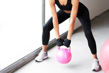Close Up Of Young Beautiful Woman Legs Doing Crossfit Russian Swing And Pink Big Ball On The Floor Of A Gym With A Pink Kettlebell . White Background Horizontal View