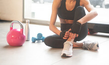Close Up Of A Blue Dumbbell On The Floor Of A Gym With A Pink Kettlebell And A Young Woman Sitting Down Isolated Horizontal