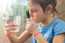 The Child Examines The Water With A Magnifying Glass In A Glass. Selective Focus.
