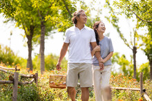 Happy Mature Couple Strolling In Park With A Birdcage