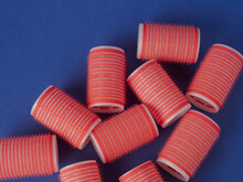 Several Red Curlers On A Blue Background
