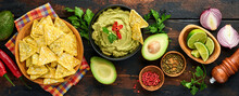 Guacamole. Traditional Latinamerican Mexican Dip Sauce In A Black Bowl With Avocado And Ingredients And Corn Nachos. Avocado Spread. Top View. Copyspace