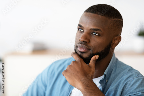 Fototapeta Portrait Of Thoughtful Black Millennial Man Touching Chin And Looking Away