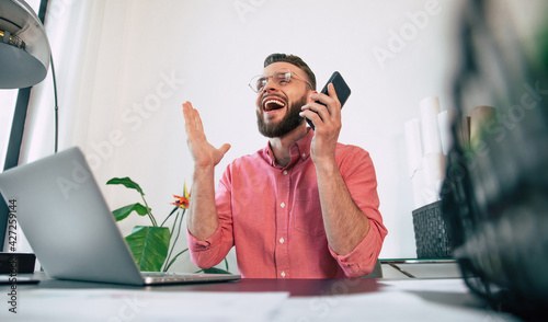 Canvas Excited happy handsome bearded man in casual clothes is smiling and shouting due
