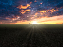 Dramatic Sunrise In A Field Where The Sun Touches The Horizon With Birds And A Stroller