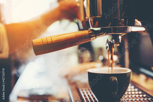 Obraz barista person making coffee in cafe, hot drink cup from espresso machine, beverage restaurant business, vintage filter image - fototapety do salonu