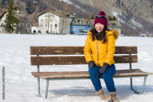 Fototapeta unique Winter holidays trip to amazing snow valley - young happy and beautiful Asian woman sitting on bench alone enjoying snowy mountain view obraz na płótnie