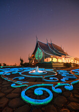 Wat Sirindhorn Wararam Temple Or Wat Phu Prao With Asian Woman Sitting On Glowing Sculpture And Illuminated Church In The Night At Ubon Ratchathani