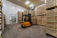 Forklift Lifting Crates With Fruits. Cold Storage Interior.
