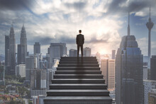 Ambition Concept With Confident Businessman On The Top Of Stairway And Looking On City Skyline