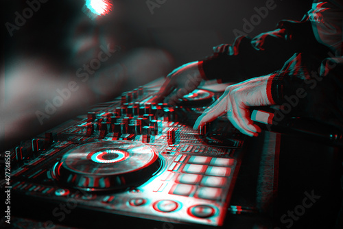 Fototapeta DJ console for mixing music with hands and with blurred people at a night club. Black and white with 3D glitch virtual reality effect obraz