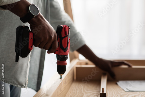 Obraz Unrecognizable black man assembling table, screwing details of desk with electric drill, closeup, crop - fototapety do salonu