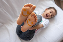 Close Up Of Little Girl's Feet Painted With Smiles.