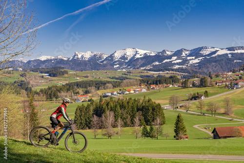 Stampa su Tela senior woman mountainbiking below the Nagelfluh mountain chain with Hochgrat sum