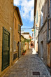 A narrow street between the old buildings of Macerata, a medieval town in the Marche region.