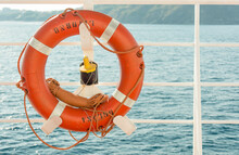 An Orange Lifebuoy Attached To The Railing Of A Ship Or Ferry Against The Backdrop Of The Blue Sea And Mountains.