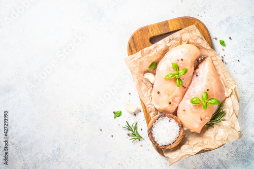 Chicken fillet with spices and herbs at white table.