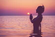 Silhouette Of Young Woman Practicing Yoga On The Beach At Sunrise