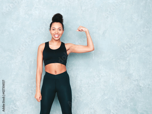 Fitness smiling black woman in sports clothing with afro curls hairstyle.She wearing sportswear. Young beautiful model with perfect tanned body.Female shows her muscles in studio near gray wall