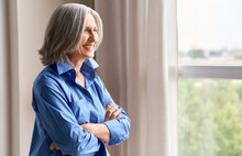 Mature Happy Laughing 60s Middle Aged Business Woman Standing Indoors In Home Office, Arms Crossed. Senior Elder Elegant Serene Woman Looking At Window Thinking Of Positive Vision Enjoying Wellbeing.