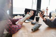 Male And Female Colleagues Holding Bionic Prosthesis Limbs And Discussing It