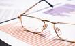 closeup glasses on financial newspaper under light tint blue