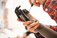 Man Scientist Twisting With Screwdriver Contacts In Mechanical Plastic Hand