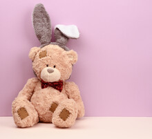 Cute Brown Teddy Bear Wearing A Rabbit Mask With Long Ears On His Head
