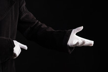 Hand Gestures. Showman Or Magician Illusionist In White Gloves On A Black Background.