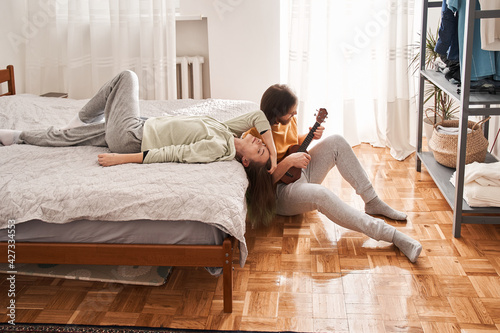 Man playing at the ukulele for his girlfriend laying at the bed at home