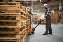 Caucasian Warehouse Worker Lifting Weight With Manual Pallet Jack. Working In Storage Room.