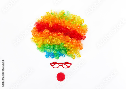 Valokuva Top view of funny clown face formed with a colorful wig, glasses, and red nose o