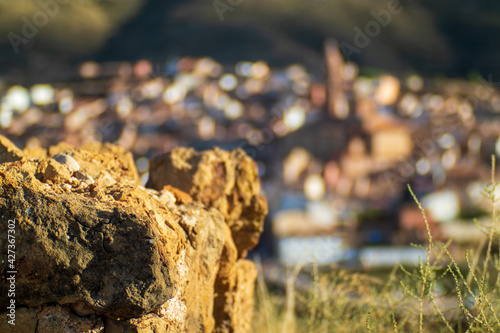 Billede på lærred Closeup shot of golden rubble rocks with a blurry defocused town landscape for b