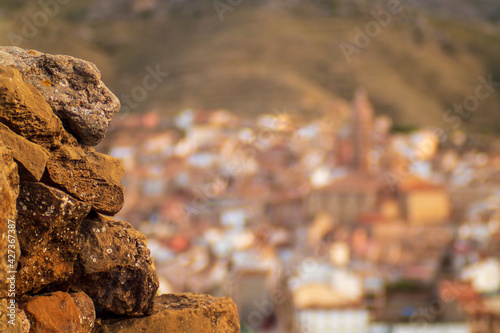 Closeup shot of golden rubble rocks with a blurry defocused town landscape for b Fototapet