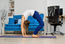 Young Woman Practicing Yoga At Home, Doing Inversion Pose