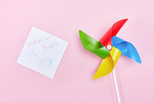 """Top View Of """"April Fools Day"""" With A Colorful Wind Spinner Isolated On Pink Background"""