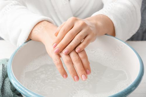 Billede på lærred Young woman undergoing spa manicure treatment in beauty salon