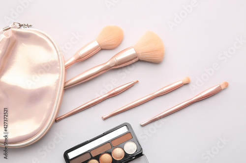 Obraz na płótnie Bag with stylish makeup brushes and eyeshadows palette on light background