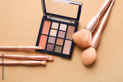 Obraz na płótnie Stylish makeup brushes and eyeshadows palette on color background