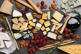 Cheese plate with grapes and nuts on dark table, flat lay