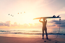 Man Hold Surfboard Standing With Birds Flying At Tropical Sunset Beach Background. Summer Vacation And Sport Adventure Concept.