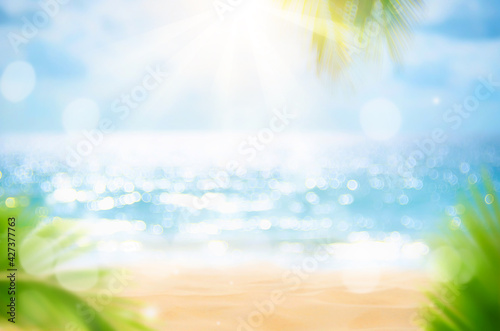 Obraz na plátně Blur beautiful nature green palm leaf on tropical beach with bokeh sun light wave abstract background